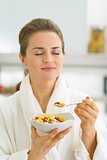 Young woman enjoying muesli in kitchen