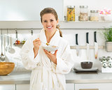 Portrait of smiling young woman eating muesli in kitchen in the