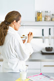 Young woman eating muesli in kitchen in the morning. rear view