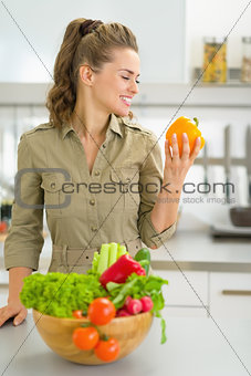 Portrait of young housewife with fresh vegetables in modern kitc