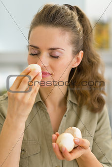 Portrait of young housewife smelling mushroom