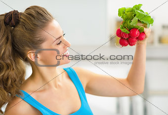 Portrait of happy young woman holding radishes