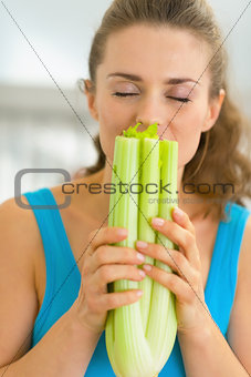 Portrait of young woman smelling fresh celery