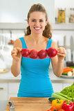 Happy young woman showing onion in kitchen
