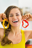 Portrait of happy young woman using bell pepper slices as earrin