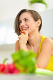 Young woman eating tomato in kitchen