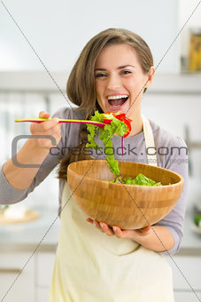 Portrait of happy young housewife tasting salad in kitchen