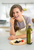 Portrait of happy young housewife eating cheese with olives