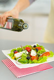 Closeup on young housewife adding olive oil in salad