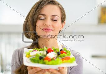 Portrait of young housewife enjoying fresh salad