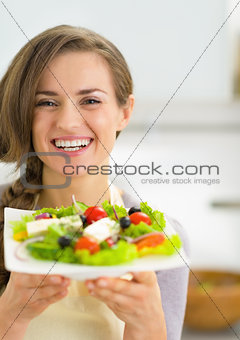 Portrait of happy young housewife showing fresh salad