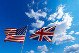 USA and UK flags in the blue sky