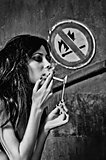 "Beautiful young woman lights cigarette near ""No fire and smoking"" sign"
