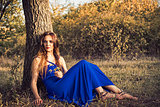 Beautiful young woman sitting under tree. Sunset time