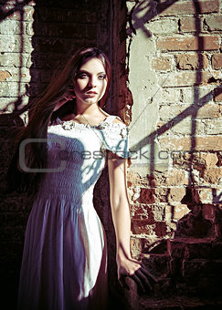 Dramatic portrait of beautiful young woman in white dress