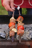 meat roasted on the fire skewers (shashlik) with tomatoes and mushrooms man in the background