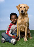 boy and a Golden Retriever sitting on the grass