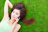 smiling girl lying down on a meadow  and talking by smartphone