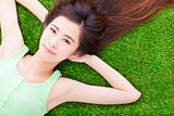 sunny pretty girl lying down on a meadow
