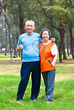 smiling senior couple holding badminton racket in the park