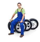 Friendly car mechanic sitting on tires