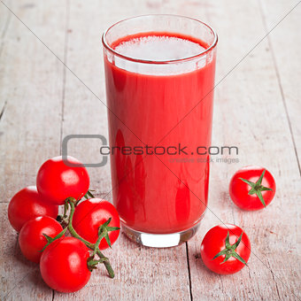tomato juice in glass and fresh tomatoes