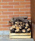 dry chopped firewood logs in a pile on the brick wall background