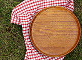 empty wooden plate on a background of green grass
