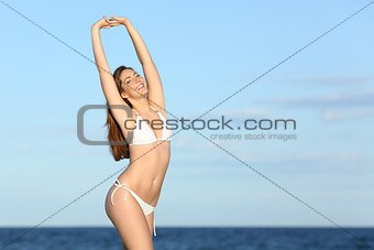 Fitness happy woman with perfect body on the beach