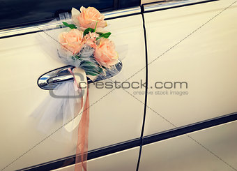 Door of white wedding car with flowers and white bow