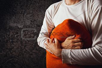 Man hugging orange pillow