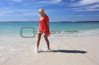 Happy woman splashing feet at the beach