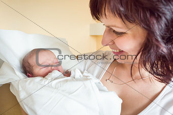 Loving mother embracing her newborn baby