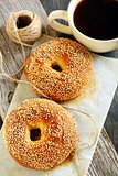 Bagels with sesame seeds and black coffee.