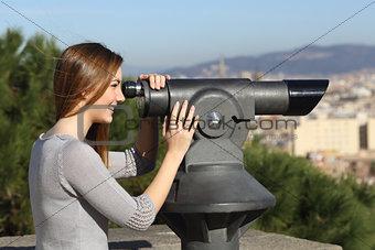 Tourist woman watching city through a telescope
