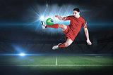 Fit football player jumping and kicking