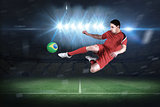 Fit football player jumping and kicking
