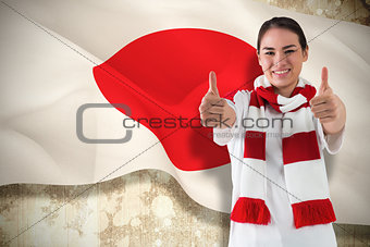 Football fan in white wearing scarf showing thumbs up