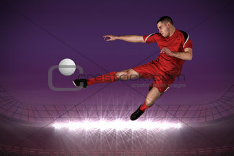 Fit football player playing and kicking