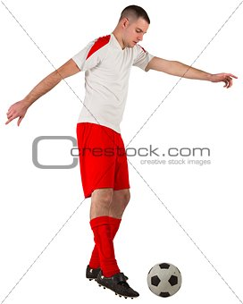 Fit football player playing with ball