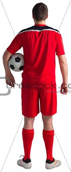 Football player wearing red gear standing with ball