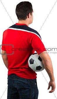 Football fan in red jersey holding ball