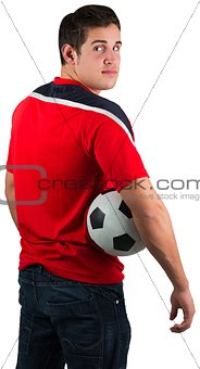 Football fan in red jersey holding ball