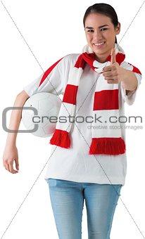 Football fan in white wearing scarf holding ball