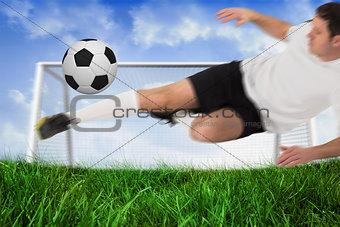Football player in white kicking ball