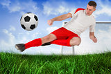Fit football player playing and kicking ball