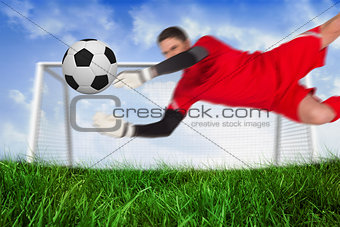 Fit goal keeper jumping up saving ball