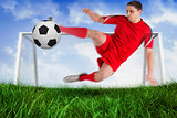 Fit football player jumping and kicking ball
