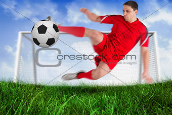 Fit football player jumping and kicking ball