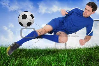 Football player in blue kicking the ball